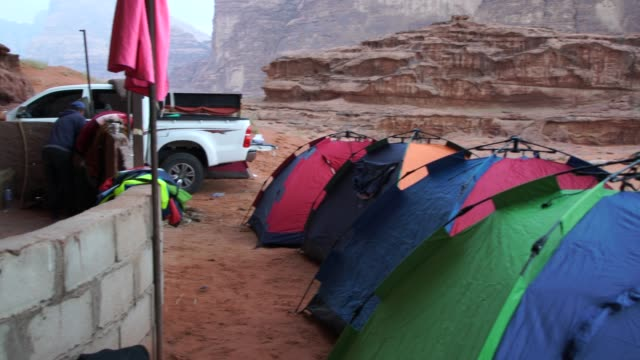 wild camp tents pitched near dramatic rocks n wadi rum desert  early in the morning - riverbed stock videos & royalty-free footage
