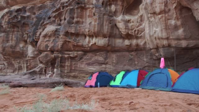 wild camp tents pitched near dramatic rocks n wadi rum desert  early in the morning - eco tourism video stock e b–roll