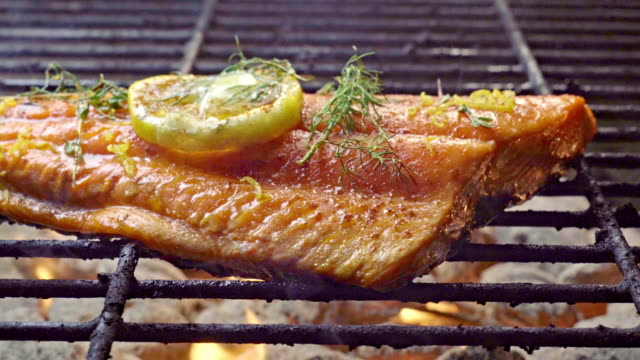 vídeos de stock e filmes b-roll de wild caught salmon filet on a fiery grill topped with lemon slice and herbs - marisco