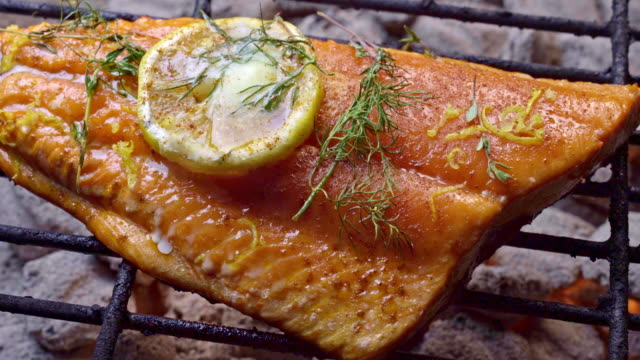 wild caught salmon filet on a fiery grill topped with lemon slice and herbs - salmon seafood stock videos & royalty-free footage