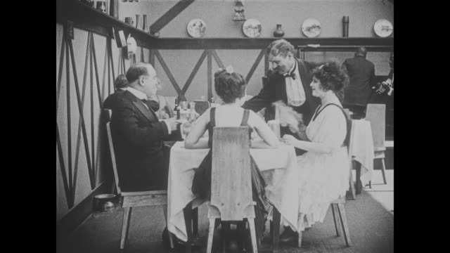 1918 wildly mustached waiter patiently takes order from man and three female companions - menu stock videos & royalty-free footage