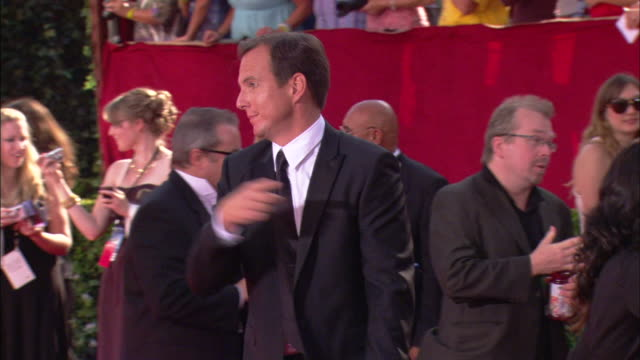 will arnett pointing and speaking to someone and waving as he rushes down crowded red carpet at nokia theater - ウィル アーネット点の映像素材/bロール