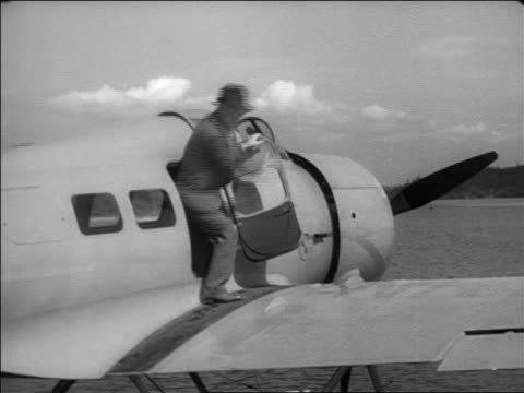 vidéos et rushes de will rogers climbing into side door of hydroplane outdoors / documentary - 1935