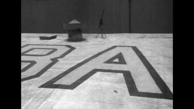 vídeos de stock, filmes e b-roll de vs will rogers jr and virginia gibson walk along looking at huge letters burbank on slanted roof / pan of letters and the couple walking to worker... - pintor artista