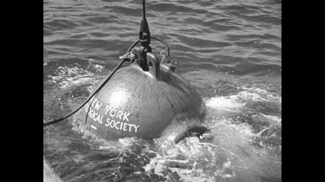 vídeos y material grabado en eventos de stock de william beebe and otis barton undersea explorers on boat off the coast of bermuda / cable lowers the two in their bathysphere into the water / beebe... - cable de acero