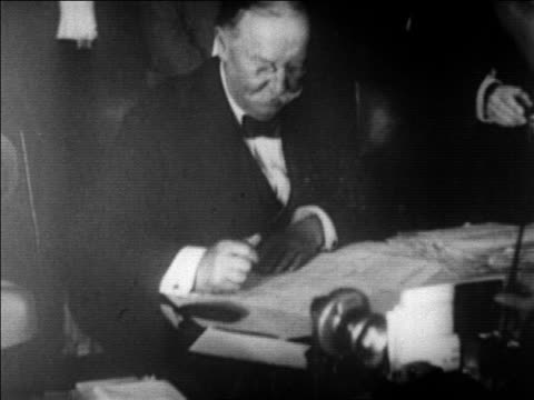 stockvideo's en b-roll-footage met william h taft signing document at desk as chief justice of the supreme court / newsreel - 1921