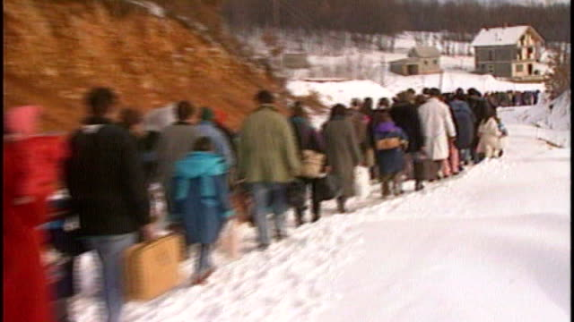 stockvideo's en b-roll-footage met william hague calls for justice for war rape victims tx long line of bosnian refugees trudging along through snow soldiers standing guard legs of... - slachtoffer