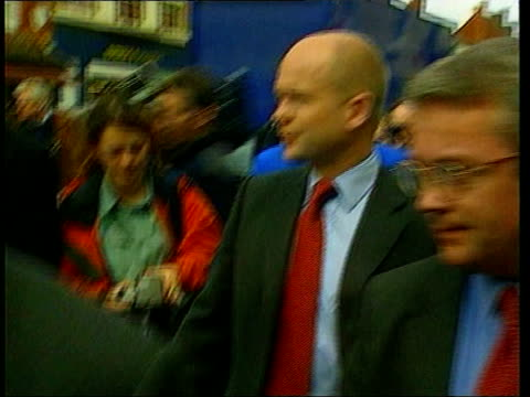 william hague joins norfolk farmer debate; itn england: oxfordshire: witney: ext william hague mp towards past along street with others - oxfordshire stock videos & royalty-free footage