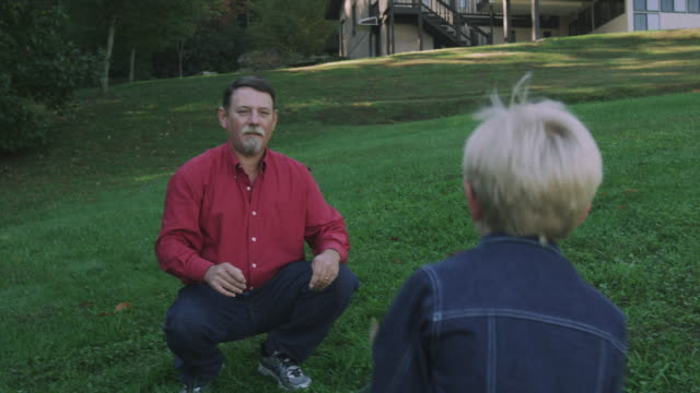 stockvideo's en b-roll-footage met william hayes hugs his grandfather charles as they play football. - kleinzoon