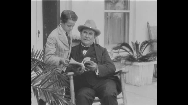 william jennings bryan sits in a porch chair thumbing through a book as his grandson john bryan looks on - william jennings bryan stock videos & royalty-free footage