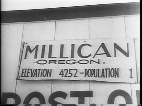 william rahn tacking up 'for sale' sign at the millican or post office / sign for millican or 'population – 1' / rahn posing with list of his jobs /... - 画鋲点の映像素材/bロール