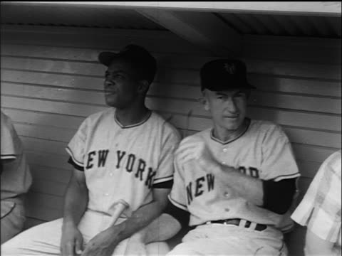 vídeos de stock e filmes b-roll de willie mays smiling sitting next to manager bill rigney in dugout / ny giants - camisola de basebol