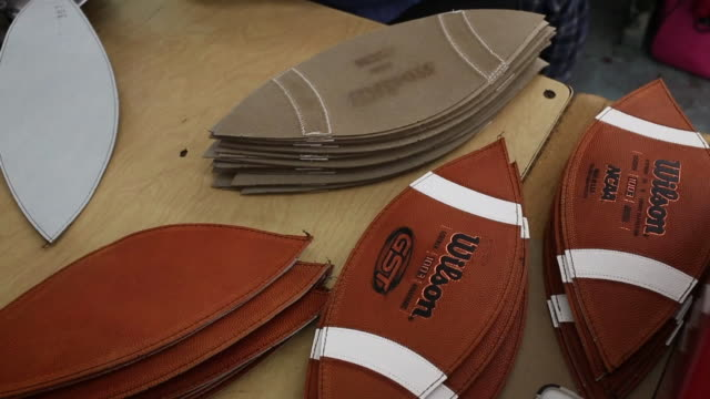 wilson footballs are manufactured at the wilson sporting goods company factory in ada, ohio, us, an employee cuts football shaped pieces out of a... - sports equipment stock videos & royalty-free footage