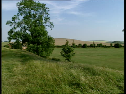 wiltshire plains with silbury hill in distance pan left to avebury stone circle - avebury stock videos & royalty-free footage