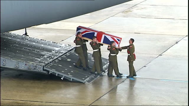 stockvideo's en b-roll-footage met lyneham: ext soldiers carrying union-flag draped coffin containing body of british soldier lance corporal james hill off plane in repatriation... - repatriëring