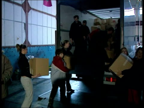 raf wroughton base human chain loading boxes of food and clothing onto truck pan volunteers sorting through boxes in warehouse huge pile of boxes of... - 2004 stock-videos und b-roll-filmmaterial