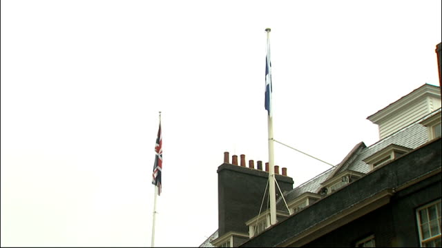 scottish flag raised over downing street england london 10 downing street ext various of workmen lowering union jack and raising scottish flag over... - lowering stock videos & royalty-free footage