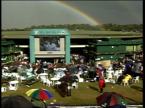 wimbledon championship: today's matches; itn ext tbv crowd on henman hill watching giant screen with rainbow over centre court in b/g - itvイブニングニュース点の映像素材/bロール