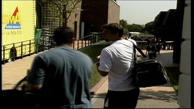 goran ivanisevic arrives / tim henman fans; itn england: london: wimbledon: ext goran ivanisevic across road and along into grounds of wimbledon / bv... - sportlerin stock-videos und b-roll-filmmaterial