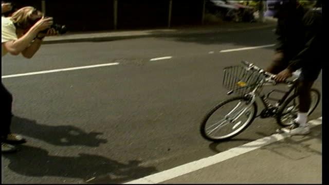interview with richard williams; itn england: london: wimbledon: ext richard williams unlocking bicycle and gets on bicycle / richard williams on... - international tennis federation stock videos & royalty-free footage