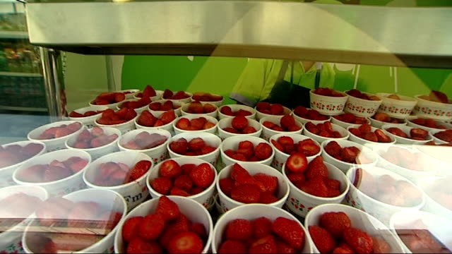 wimbledon lawn tennis championships: day one; punnets of strawberries and cream for sale, customers buying them and adding sugar - international tennis federation stock videos & royalty-free footage