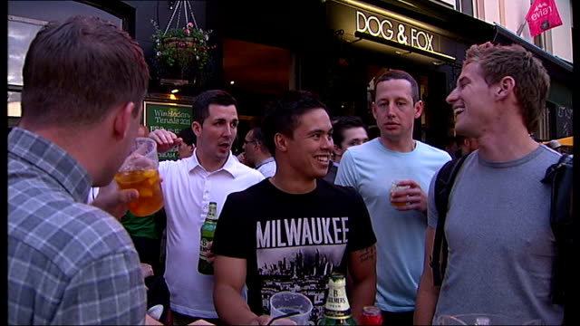 nadal and djokovic reach men's final; england: london: wimbledon: ext men seen eating inside restaurant people eating and drinking at table outside... - international tennis federation stock videos & royalty-free footage