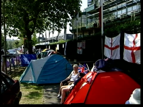London Wimbledon Row of tents on pavement outside Wimbledon entrance as queuing for tickets GV Fans sitting in tent MS Fan in tent Vox pops GV Tennis...