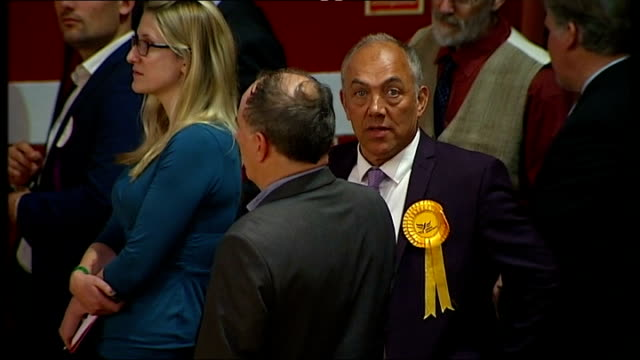 vídeos de stock e filmes b-roll de win clacton by-election and narrowly beaten in middleton and heywood by-election; essex: clacton-on-sea: int men along in hall pull focus ext / night... - retrovírus