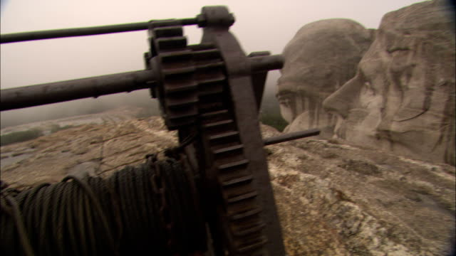 vidéos et rushes de a winch is seen on a ledge next to mount rushmore. - monument national du mont rushmore