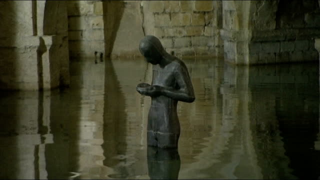 hampshire winchester winchester cathedral various of flooded crypt of winchester cathedral with partlysubmerged sculpture statue 'sound ii' by... - crypt stock videos and b-roll footage