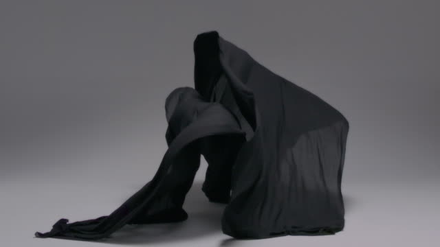 Wind blowing black cloth as it falls to the ground