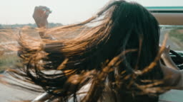 SLO MO Wind blowing hair of carefree woman driving convertible along sunny, rural field