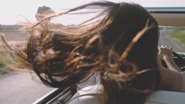 cu slo mo wind blowing hair of carefree young woman driving convertible along sunny, rural field - wind stock videos & royalty-free footage
