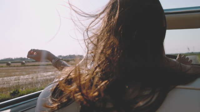 slo mo - time warp effect wind blowing hair of carefree young woman driving convertible along sunny, rural field - windswept stock videos & royalty-free footage
