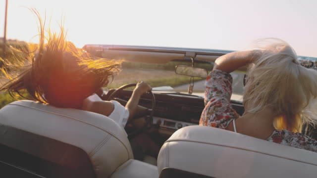 ms slo mo wind blowing hair of carefree young women driving convertible along sunny, rural road - retro convertible stock videos & royalty-free footage