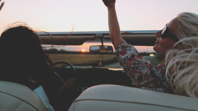 slo mo - time warp effect wind blowing hair of carefree young women driving convertible on rural field at sunset - capelli lunghi video stock e b–roll
