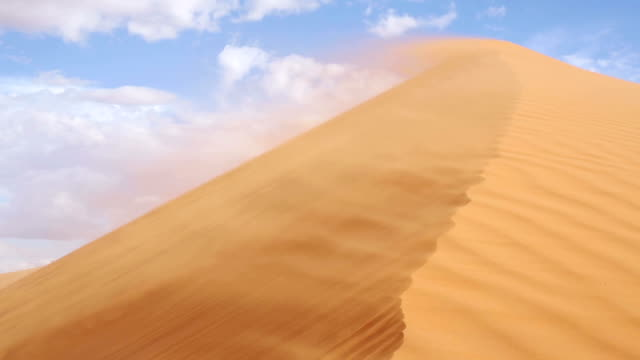 stockvideo's en b-roll-footage met wind blowing sand across the dunes of sossusvlei - namibië