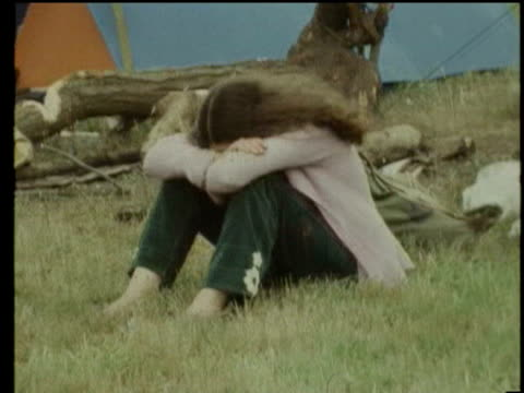 stockvideo's en b-roll-footage met wind blowing tents at glastonbury festival / mother feeding child in field / ms cu people walking down muddy path / la ws pan tu men on scaffolding... - blootvoets
