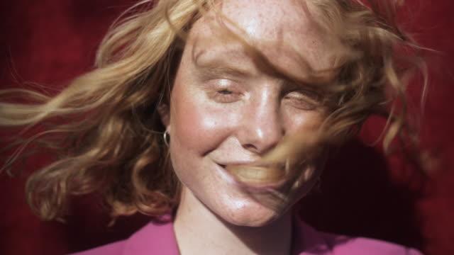 vídeos de stock e filmes b-roll de wind blows caucasian woman's hair, portrait - fundo colorido