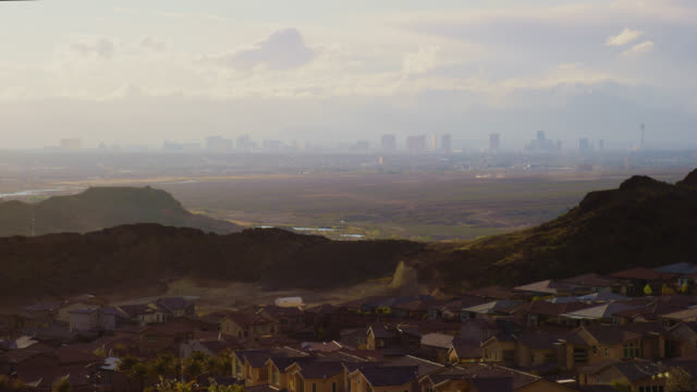 wind blows dust clouds over a desert landscape between a residential neighborhood in the foreground and a hazy las vegas city skyline in the background at sunset - dust storm stock videos & royalty-free footage