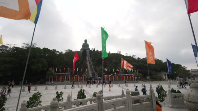 wind blows flags in front of tian tan buddha, pov - tian tan buddha stock videos and b-roll footage