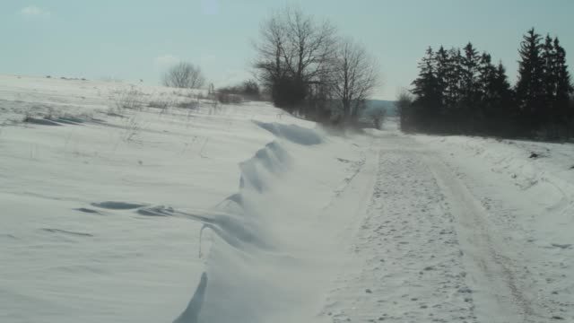 Wind blows the snow off a drift onto a snow-covered road.