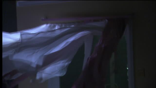 Wind blows through a broken window.