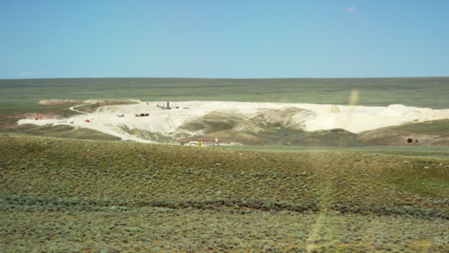 wind blows wild grasses in the foreground while a mine sits in the middle of the prairie in the background under a sunny, clear sky in northern wyoming - grass area stock videos & royalty-free footage