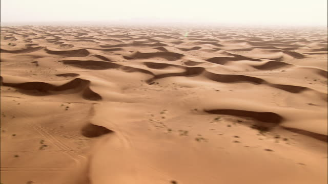 vidéos et rushes de aerial wind carves rippling patterns in desert sand, dubai, united arab emirates - dubai