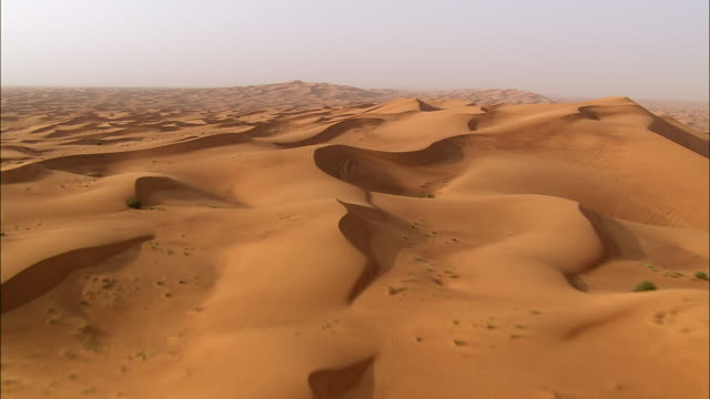 vidéos et rushes de aerial wind carves rippling patterns in desert sand, dubai, united arab emirates - aride