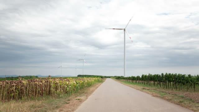 wind-energie und landwirtschaft, zeitraffer - ländliche straße stock-videos und b-roll-filmmaterial