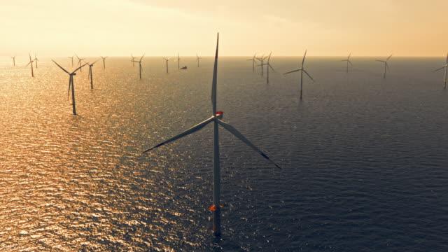 stockvideo's en b-roll-footage met aerial wind park op zee in zonsondergang - windenergie