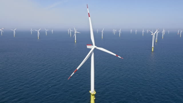 aerial wind farm at sea in sunshine - tilt down stock videos & royalty-free footage