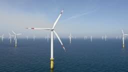 AERIAL Wind farm at sea in sunshine